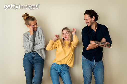 Three friends in front of a yellow wall, having fun - gettyimageskorea