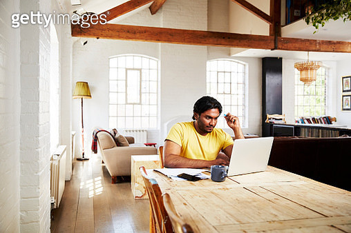 A guy wearing a yellow t-shirt works from home using his dining room table as a desk - gettyimageskorea