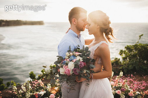 Sunset wedding ceremony outdoors in Bali. Young couple kissing in love - gettyimageskorea