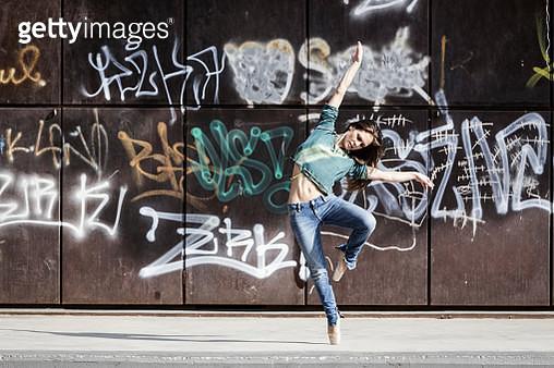 Full Length Of Woman Dancing Against Graffiti On Wall - gettyimageskorea