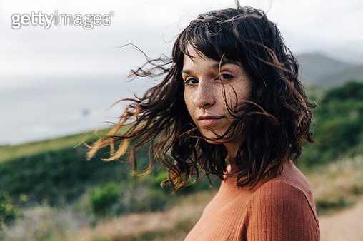 Portrait of confident woman with freckles standing against sky - gettyimageskorea