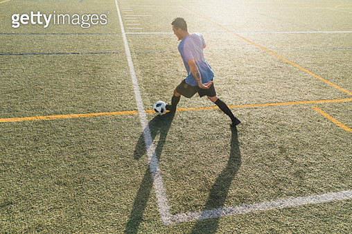 High angle view of soccer player kicking ball on field - gettyimageskorea