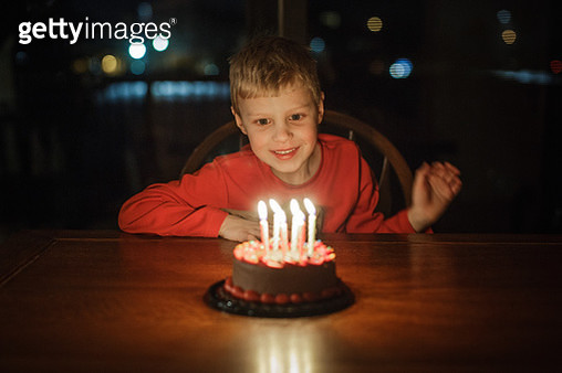 Little boy smiles at his birthday cake - gettyimageskorea