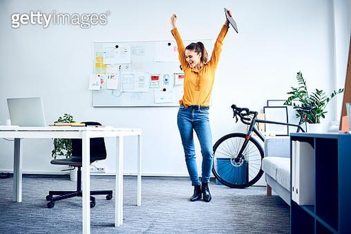 Happy young businesswoman cheering in office - gettyimageskorea