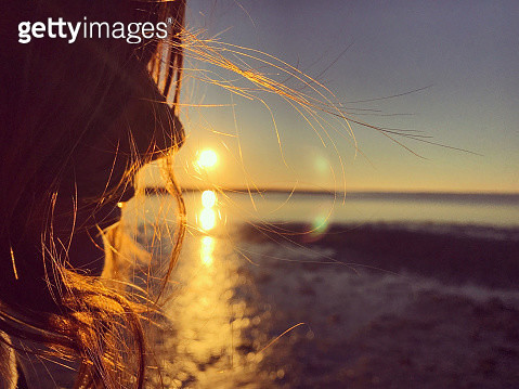 Portrait of a girl in profile, silhouetted against a golden orange sunset as she stands at the water's edge on Assateague Island. Travel. Nature. - gettyimageskorea