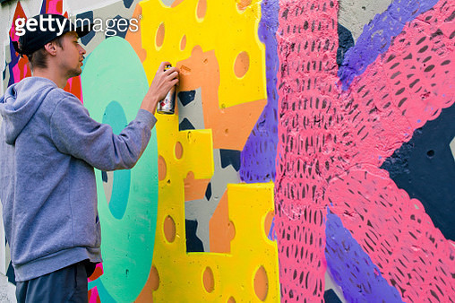 Side View Of Street Artist Painting Graffiti On Wall - gettyimageskorea