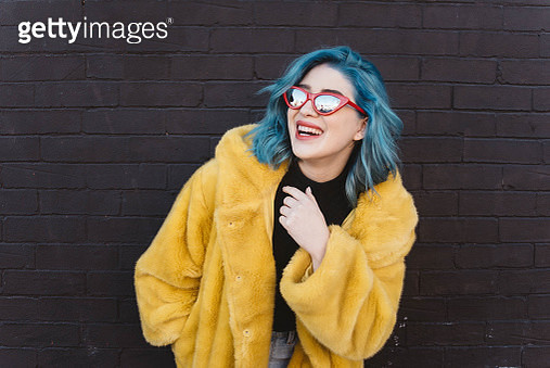 Smiling Woman Wearing Coat And Sunglasses While Standing Against Brick Wall - gettyimageskorea