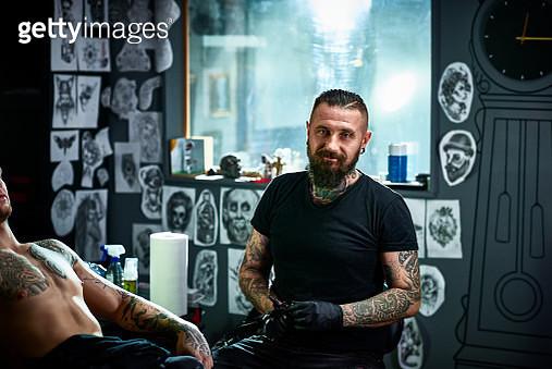 Portrait of male tattoo artist in tattoo parlour facing camera - gettyimageskorea