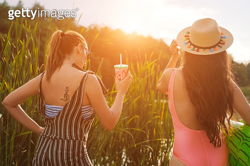 two woman enjoying by the lake at sunset - gettyimageskorea