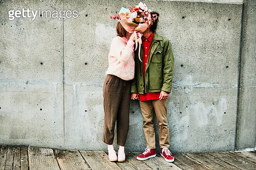 Portrait of couple kissing while hidden behind bouquet of flowers - gettyimageskorea