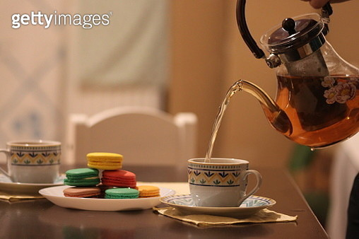 Tea Pouring Into Cup With Macaroons On Table - gettyimageskorea