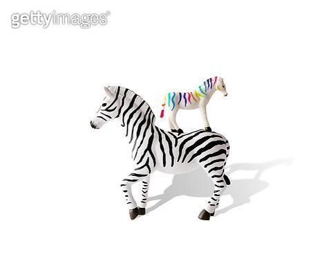 Rainbow striped zebra toy stacked on a black and white zebra toy. - gettyimageskorea