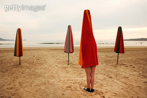 An unrecognizable  woman posing as a beach umbrella on a beach - gettyimageskorea