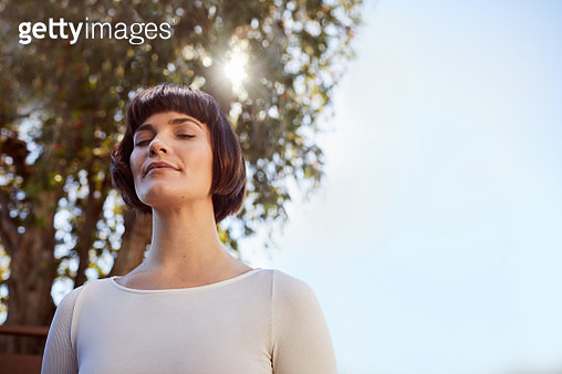 Young woman in sportswear standing outside and meditating with her eyes closed alone on a sunny afternoon - gettyimageskorea