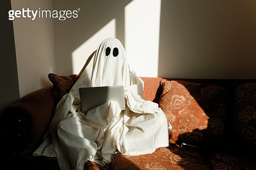 Man in ghost costume using laptop computer while sitting on sofa against wall at home - gettyimageskorea