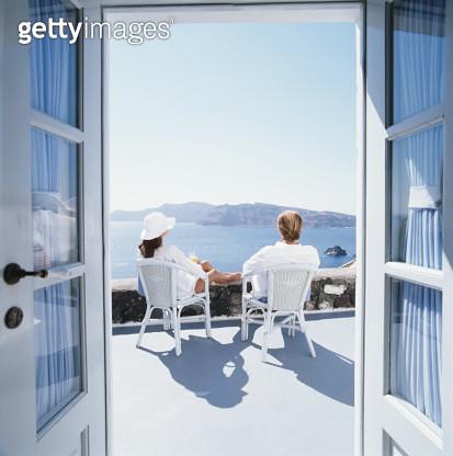 Couple sitting on balcony overlooking ocean, view through doorway - gettyimageskorea