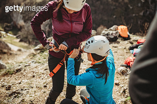 Woman with climbing instructor preparing for an outdoor rock climbing - gettyimageskorea