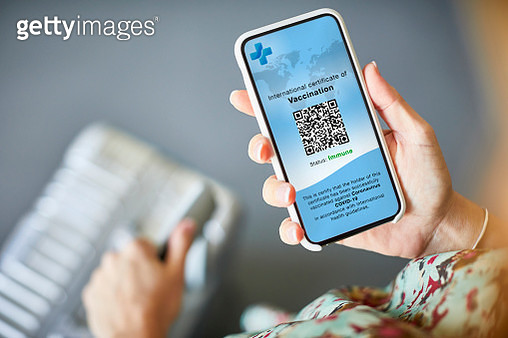 Woman Checking Covid-19 Vaccine Passport On Cellphone - gettyimageskorea