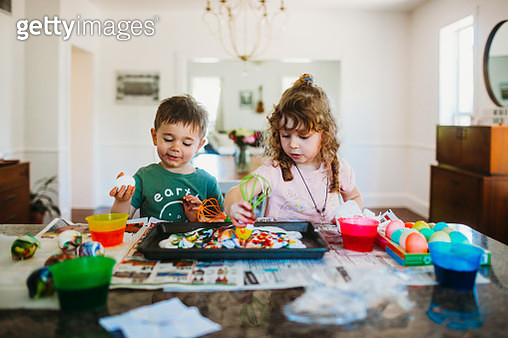 Young boy and girl sitting at kitchen counter dying easter eggs - gettyimageskorea
