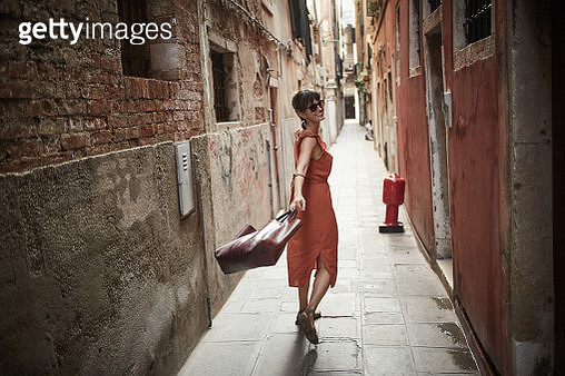 A young woman walks joyfully down Venice street - gettyimageskorea