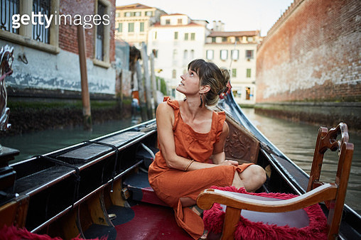 A young woman rides a gondola through Venice - gettyimageskorea