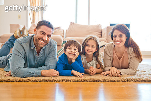 Parents and children lying together on floor in the living room and smiling at camera. Happy family staying at home due to pandemic COVID-19. - gettyimageskorea