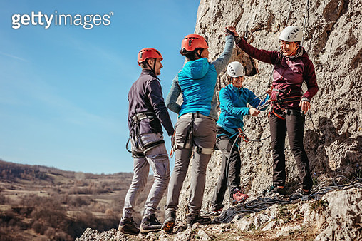 Female rock climbers giving high five after a successful climb - gettyimageskorea
