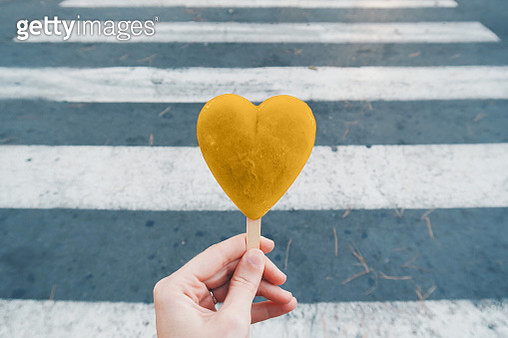 Cropped Hand Of Woman Holding Heart Shape Candy On Road - gettyimageskorea