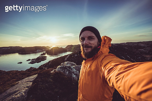 Man mountain hiking by a fjord in Norway - gettyimageskorea