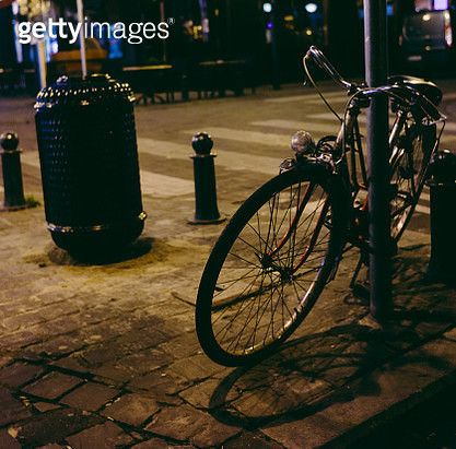 Bicycle parked at night and litter bin in the street - gettyimageskorea