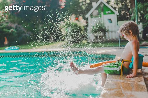 boy in swimsuit splashing in poolside in summer - gettyimageskorea
