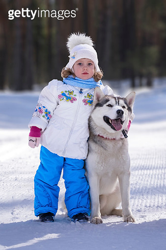 Portrait Of Cute Girl Standing By Dog On Snow Covered Field - gettyimageskorea