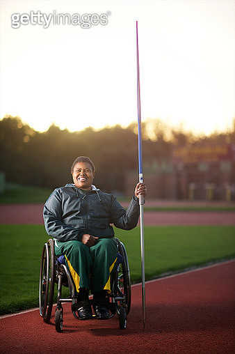 Disabled female javelin thrower in wheelchair in stadium smiling - gettyimageskorea