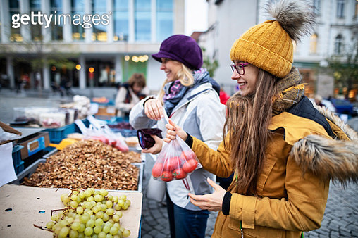 Mother and daughter buying at the Czech farmer's market.  Family is buying fresh tomatoes, walnuts and grapes. Zelny Trh, Brno old town, Czech Republic.Nikon D850 - gettyimageskorea