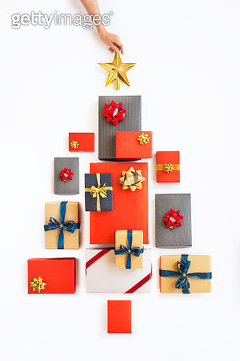 Conceptual minimalist style Christmas Day wrapped gift boxes form a Christmas tree on white background. - gettyimageskorea
