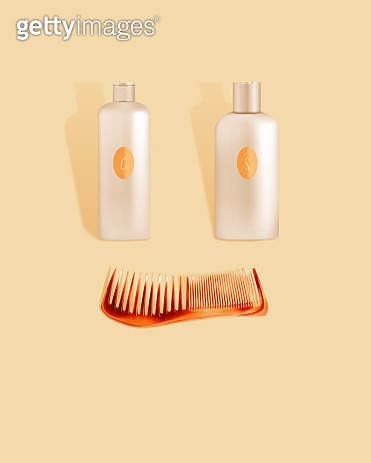 Shampoo and conditioner bottles arranged with tortishell comb to make a happy face on a cream colored background. - gettyimageskorea