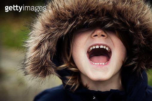 Portrait of a boy wearing a fur hood shouting - gettyimageskorea