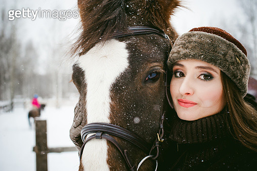 Close-Up Portrait Of Beautiful Woman With Horse During Snowfall - gettyimageskorea