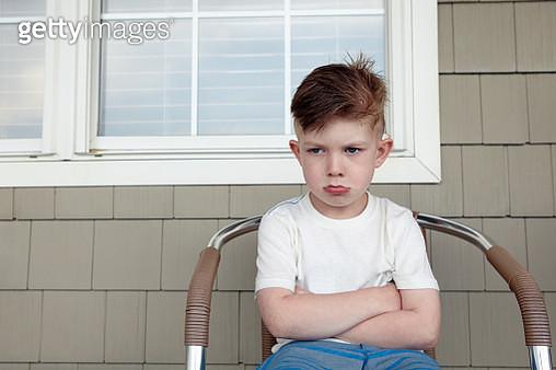 Portrait of boy sitting outside house sulking - gettyimageskorea