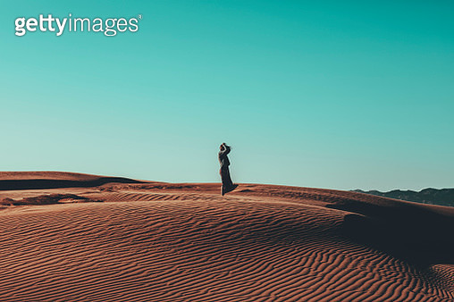 Young woman with windswept hair standing in desert landscape - gettyimageskorea