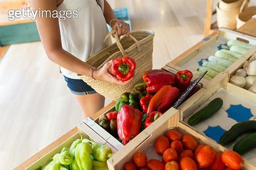 Young woman in organic store choosing vegetables - gettyimageskorea