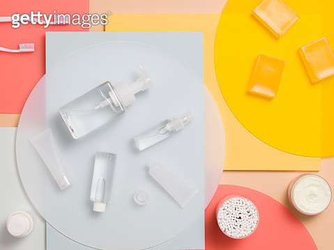 A selection of beauty products laid out on a pastel background of painted wooden surfaces and perspex sheets - gettyimageskorea