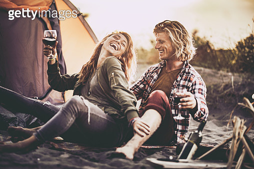 Cheerful couple having fun while drinking wine on beach camping. - gettyimageskorea