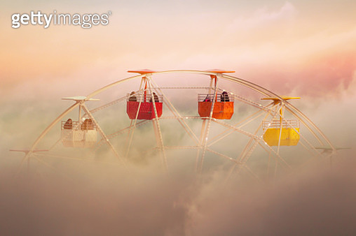 Poetical picture of ferris wheel in amusement park emerging from the clouds in a creative picture with colorful clouds during sunset time. - gettyimageskorea