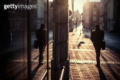 Rear View Of Silhouette Man Walking On Sidewalk - gettyimageskorea