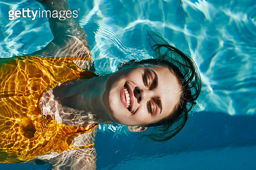 Beautiful girl in a yellow swimsuit swims in the pool and smiling - gettyimageskorea