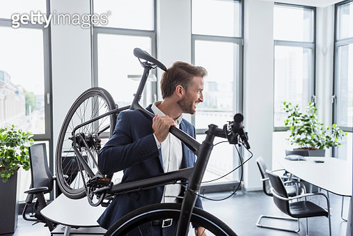 Smiling businessman with bicycle on his shoulder in the office - gettyimageskorea