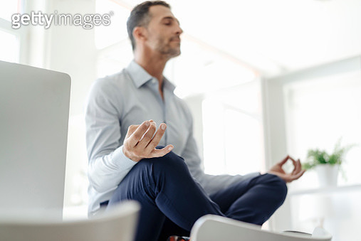 Businessman sitting on table in office practising yoga - gettyimageskorea