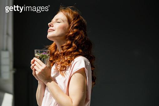 Redheaded woman enjoying sunlight - gettyimageskorea