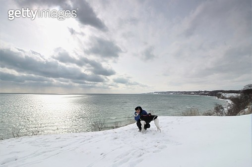 Man With Dog On Snowy Field By Lake Against Sky - gettyimageskorea